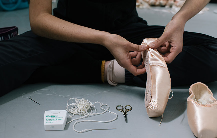 PBT dancer Marisa Grywalski sewing her pointe shoes.